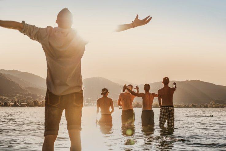 Eine Gruppe Jugendlicher, die Knietief in einem See stehen und feiern
