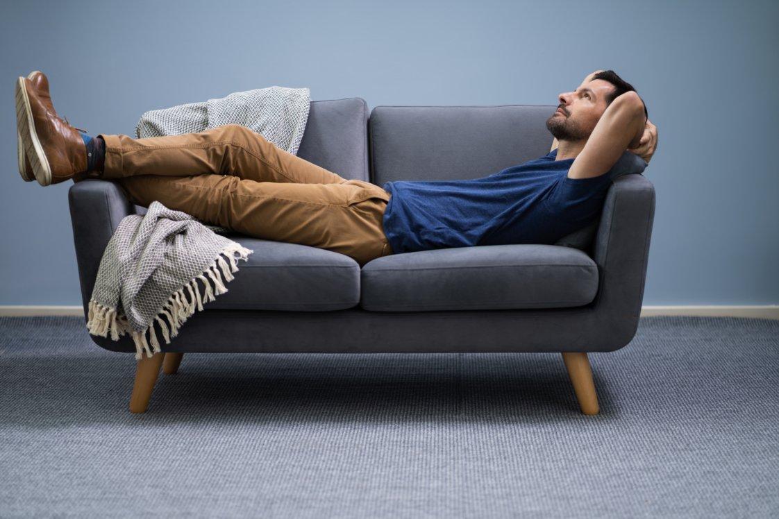 Ein Mann, der auf einer grauen Couch liegt